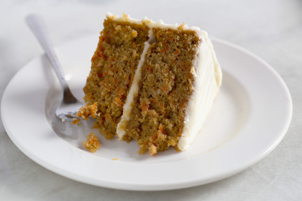 Slice of gluten-free carrot cake with cream cheese icing