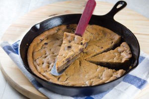 Skillet of chocolate chip cookie cake with slice taken out of it.
